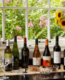 Bottles of wine line a sunny garden window for the afternoon wine hour and snacks