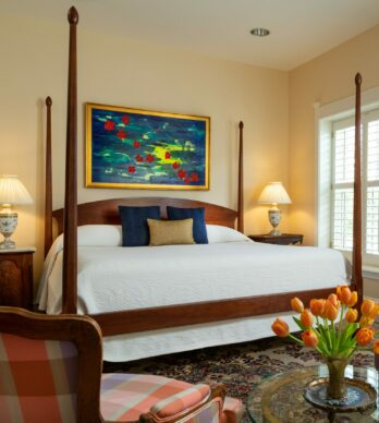 One of the elegant suites features a four poster king bed, sunny window, and seating area