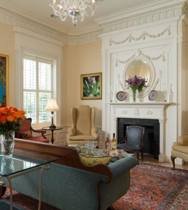 The grand living room is complete with high ceilings, a stunning fireplace, and elegant furnishings.