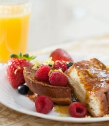 French toast with fresh raspberries, blueberries, and strawberries paired with orange juice and coffee.